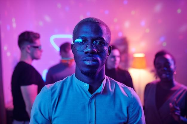 Młody poważny mężczyzna pochodzenia afrykańskiego w casualwear i okularach, patrzący na ciebie, stojąc przed przyjaciółmi na domowej imprezie