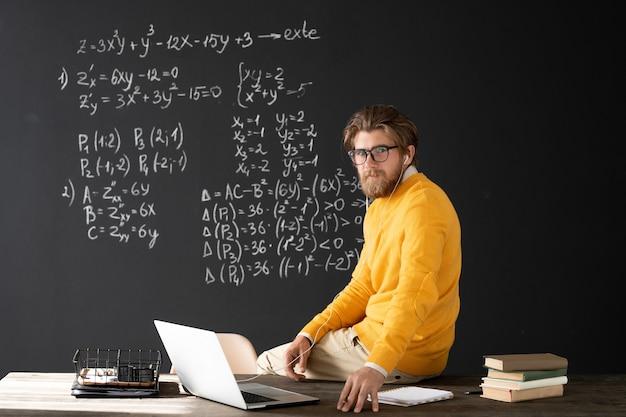 Młody poważny nauczyciel ze słuchawkami siedzi na stole na tablicy z równaniami podczas lekcji algebry online