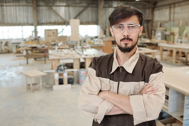 Młody poważny pracownik lub inżynier fabryki mebli w mundurach i okularach stoi przed kamerą w dużym warsztacie
