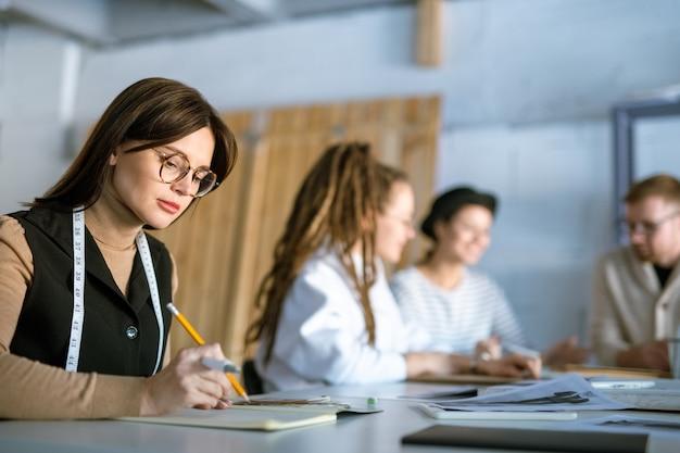 Młody poważny projektant mody brunetka z miarką na szyi i szkice w zeszycie w środowisku pracy