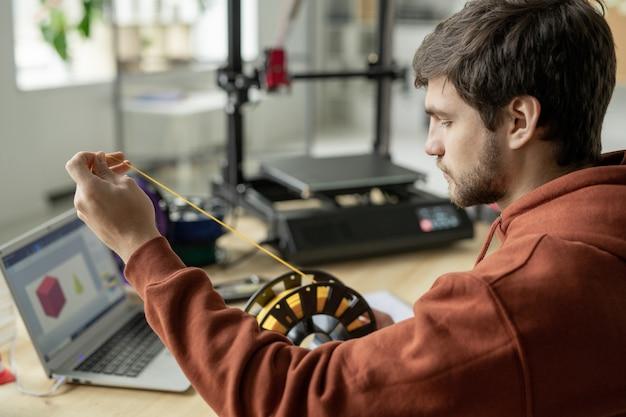 Młody poważny projektant wyciągający żółty filament ze szpuli, przygotowując się do druku 3d nowego obiektu