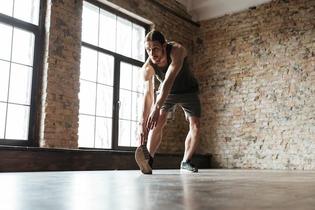Młody poważny sporta mężczyzna rozgrzewkowy przy gym