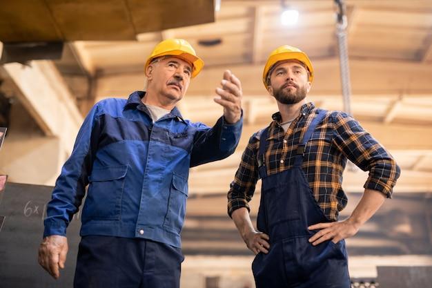 Młody poważny stażysta oglądający maszynę pokazaną przez swojego mistrza podczas wspólnej pracy w zakładzie przemysłu ciężkiego
