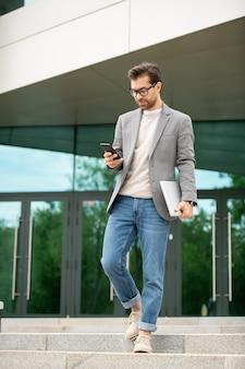 Młody, poważny, zajęty menedżer w inteligentnym dorywczo schodzący na dół podczas przewijania smartfona po pracy