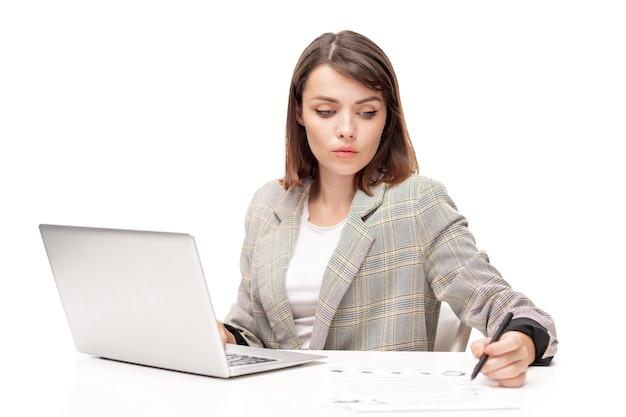 Młody poważny żeński pośrednik czytania papieru finansowego siedząc przy biurku przed laptopem