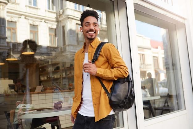 Młody pozytywny afroamerykanin w żółtej koszuli idzie ulicą słuchając ulubionej piosenki na słuchawkach, wygląda wesoło, cieszy się słonecznym dniem w mieście i szeroko się uśmiecha.