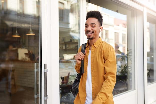 Młody pozytywny ciemnoskóry facet w żółtej koszuli słuchający ulubionej piosenki na słuchawkach, idący ulicą i fajnie wyglądający, cieszący się słonecznym dniem w mieście i szeroko uśmiechnięty.