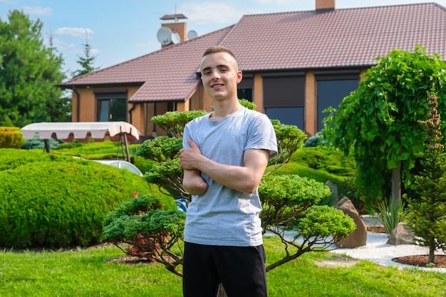 Młody pozytywny człowiek z niepełnosprawnością pozuje stojąc na zewnątrz