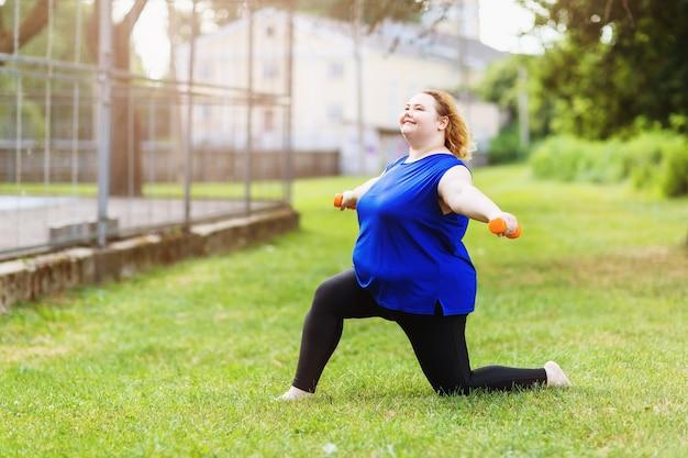 Młody pozytywny rozmiar blondynka plus wykonuje ćwiczenia z hantlami w parku