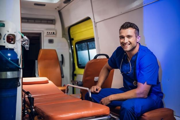 Młody pozytywny sanitariusz w niebieskim mundurze na służbie.