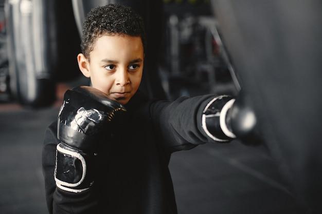 Młody pracowity bokser uczy się boksować. dziecko w centrum sportowym. dziecko podejmuje nowe hobby