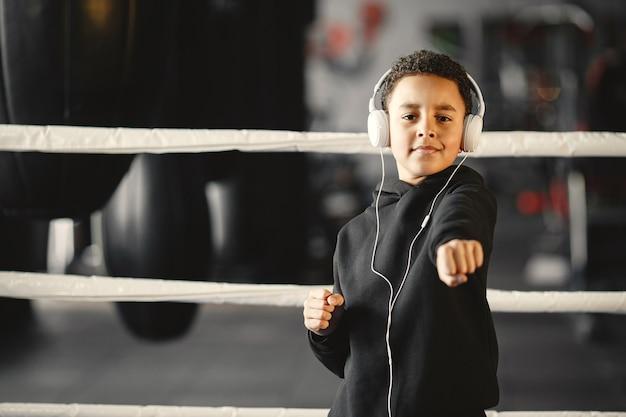 Młody pracowity bokser uczy się boksować. dziecko w centrum sportowym. dziecko ze słuchawkami.