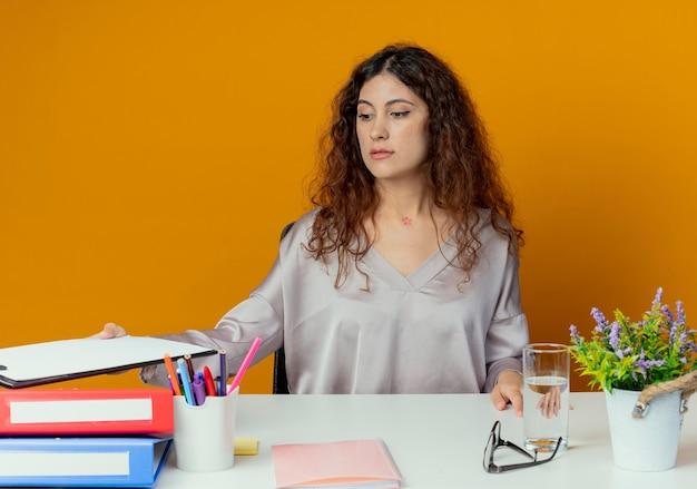 Młody Pracownik Biurowy Całkiem żeński Siedzi Przy Biurku Z Narzędzi Biurowych, Trzymając Schowka Na Bok Samodzielnie Na Pomarańczowo Darmowe Zdjęcia