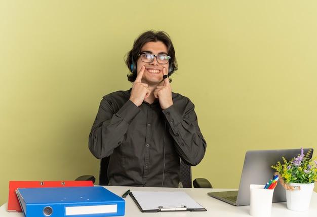 Młody pracownik biurowy mężczyzna na słuchawkach w okularach optycznych siedzi przy biurku z narzędziami biurowymi za pomocą laptopa trzyma uśmiech z palcami odizolowanymi na zielonym tle z miejscem na kopię