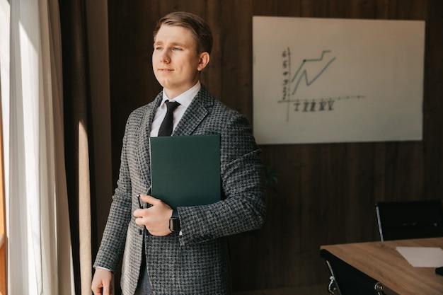 Młody pracownik biurowy o jasnej karnacji trzyma w rękach teczkę z dokumentami, stoi w swoim biurze. mężczyzna pracuje w biurze.