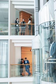 Młody pracownik biurowy stojący na balkonach i dyskutujący o pracy w nowoczesnej dzielnicy finansowej