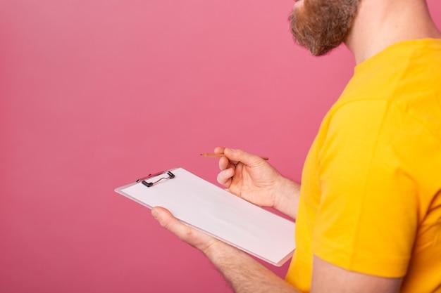 Młody pracownik brodaty mężczyzna nosić notatki na różowym tle