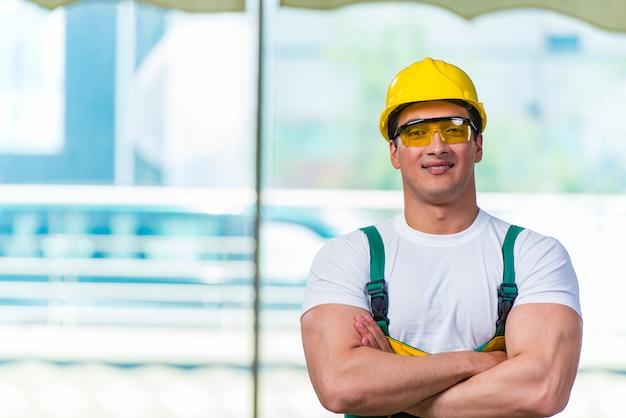 Młody pracownik budowlany pracuje na miejscu