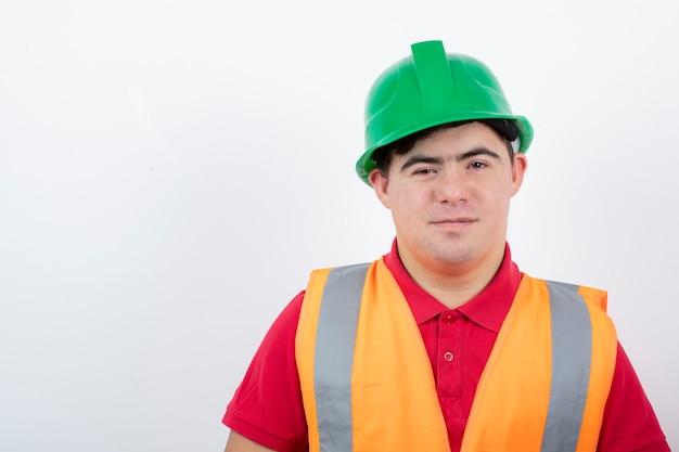 Młody pracownik budowlany w kamizelce odblaskowej stojącej i patrzącej.