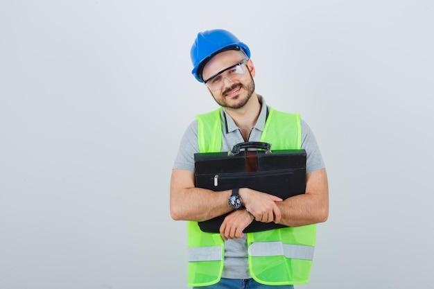 Młody pracownik budowlany w kasku ochronnym i okularach