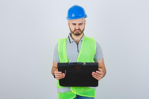 Młody pracownik budowlany w kasku ochronnym