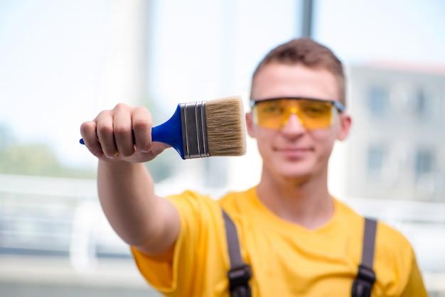 Młody pracownik budowlany w żółtych kombinezonach