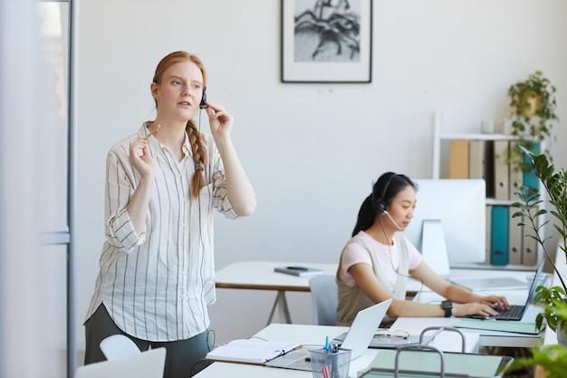 Młody pracownik call center w słuchawkach rozmawia z klientem przez telefon w biurze