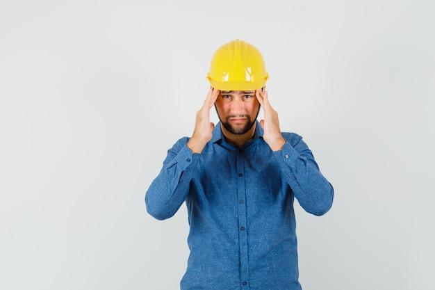Młody pracownik cierpiący na silny ból głowy w koszuli, kasku i wygląda na zmęczonego
