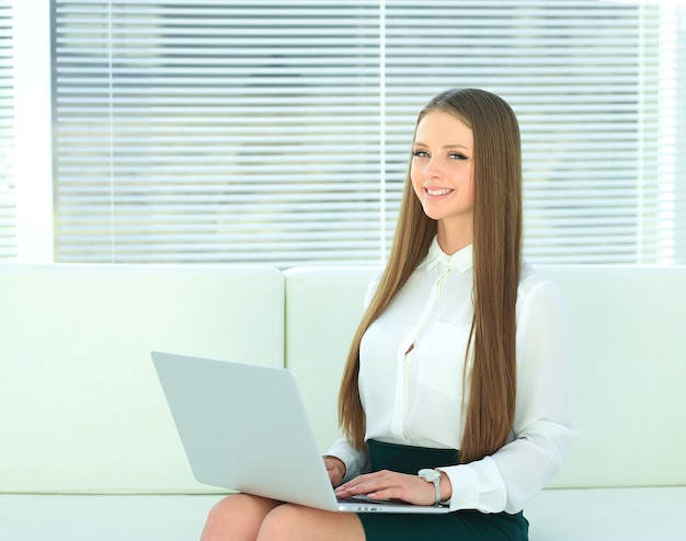 Młody pracownik firmy czytającej tekst z laptopem