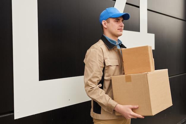 Młody pracownik fizyczny w mundurze trzymając paczki, stojąc na zewnątrz przed magazynem