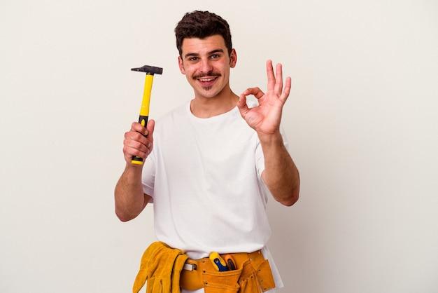Młody pracownik kaukaski mężczyzna z narzędziami na białym tle wesoły i pewny siebie, pokazując ok gest.