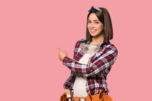 Młody pracownik kobieta wskazuje z powrotem na odosobnionej menchii ścianie