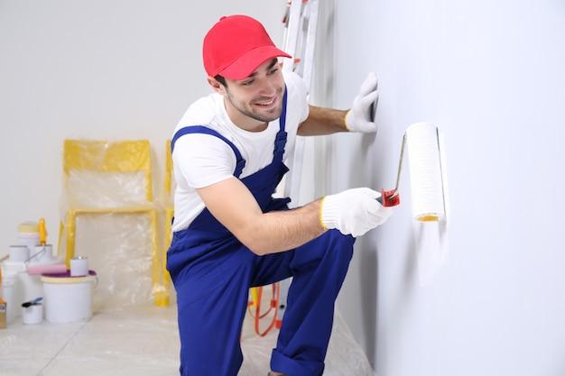 Młody pracownik malujący ścianę w pokoju