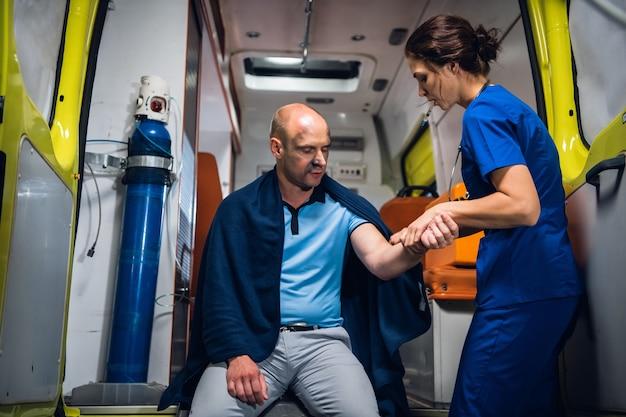 Młody pracownik medyczny sprawdza traumatyczną rękę swojego pacjenta w karetce.