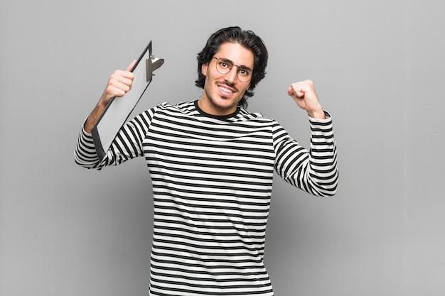 Młody pracownik mężczyzna posiadający inwentarz pokazujący gest siły z rękami, symbol kobiecej mocy