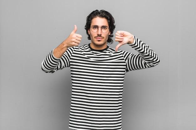 Młody pracownik mężczyzna posiadający inwentarz pokazujący kciuki w górę i w dół, trudny wybór koncepcji