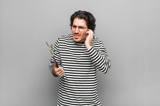 Młody pracownik mężczyzna trzyma inwentarz obejmujących uszy rękami.