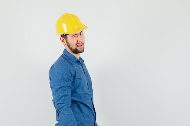 Młody pracownik mrugając okiem i patrząc na kamery w koszuli, kasku.