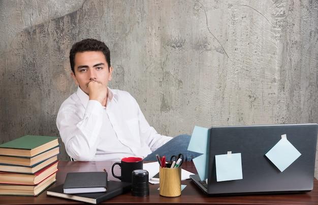 Młody pracownik myśli o czymś przy biurku.
