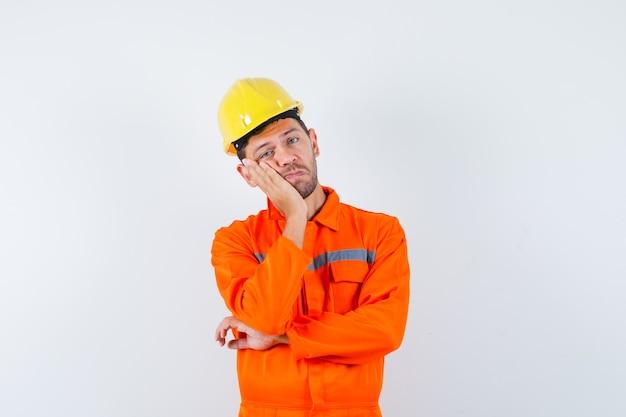 Młody pracownik oparty policzek na uniesionej dłoni w mundurze, hełmie i zamyślony.