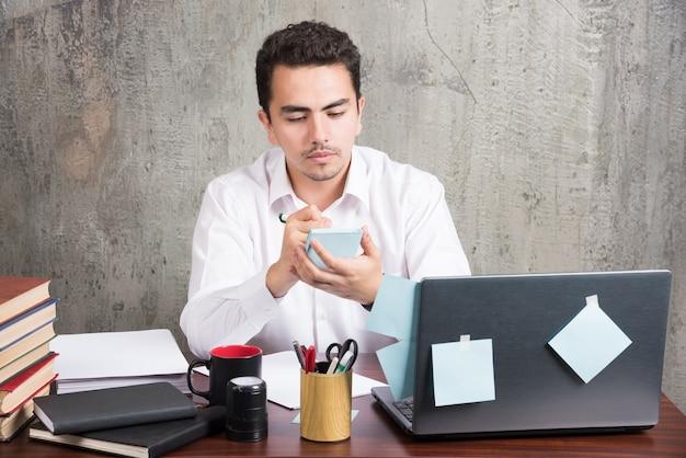 Młody pracownik patrząc jego telefon na biurku.
