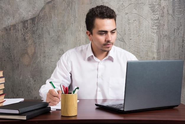 Młody pracownik patrząc na laptopa i siedząc przy biurku. wysokiej jakości zdjęcie