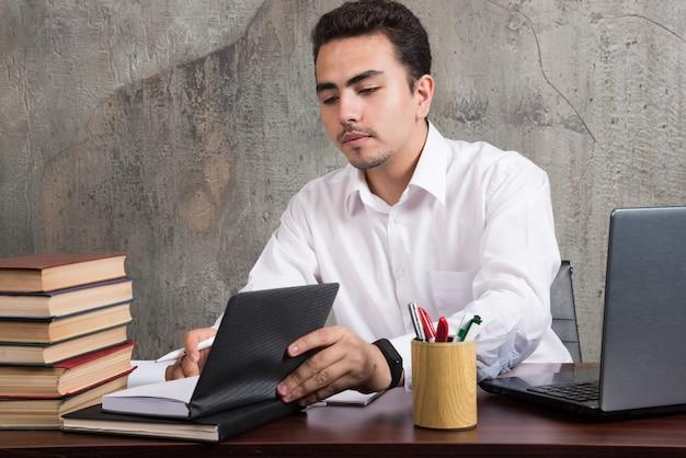Młody pracownik patrząc na notatnik i siedząc przy biurku. wysokiej jakości zdjęcie