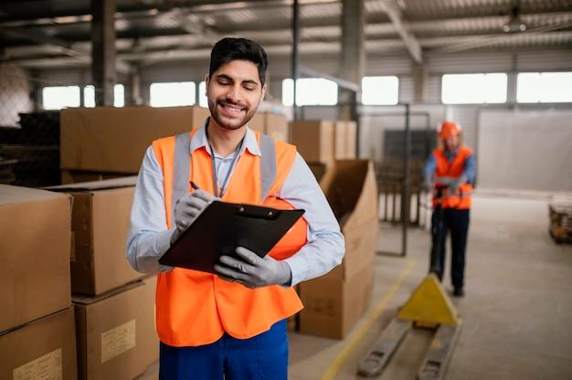Młody pracownik płci męskiej na sobie sprzęt bezpieczeństwa w pracy