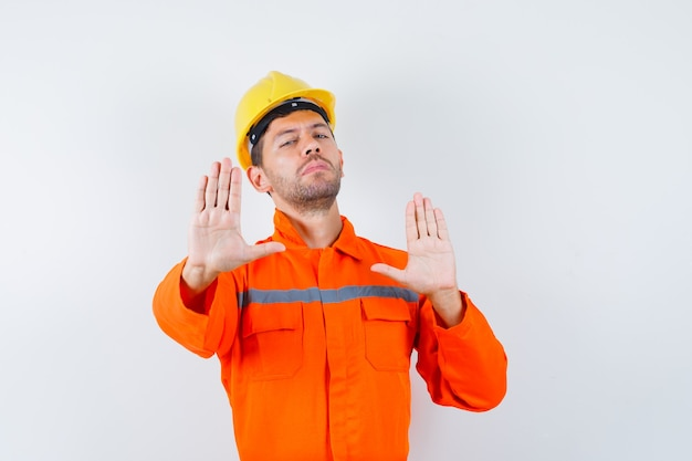 Młody pracownik pokazujący gest odmowy w mundurze, hełmie.