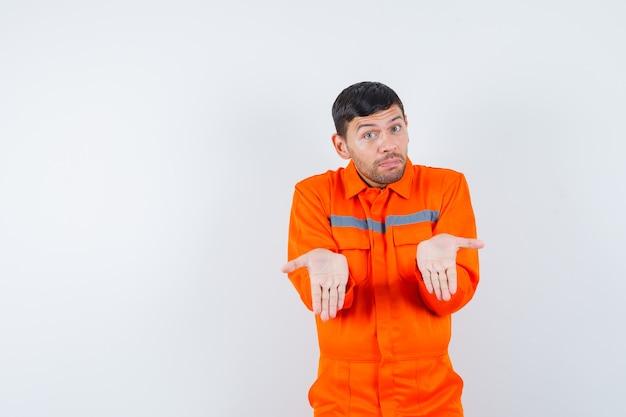 Młody pracownik pokazujący swoje puste dłonie w mundurze.