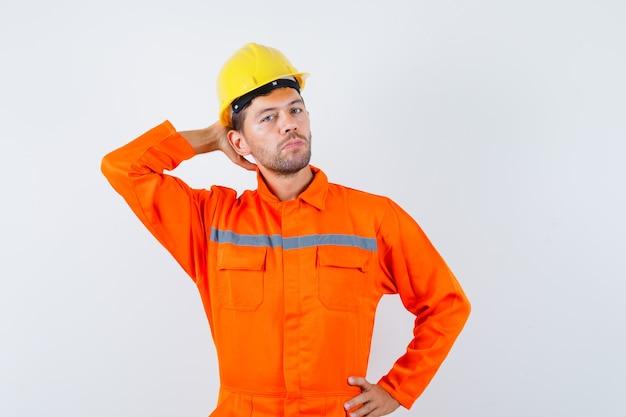 Młody pracownik pozowanie z ręką za głową w mundurze, kasku i elegancki wygląd.
