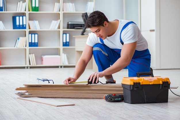 Młody pracownik pracuje na podłogowych płytach laminowanych