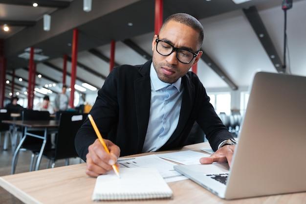 Młody pracownik robi notatki robocze w biurze