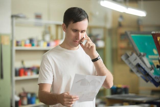 Młody pracownik rozmawia przez telefon